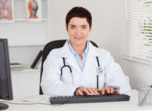 Doutor fêmea que datilografa com seu computador Foto de Stock