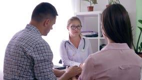 Doutor fêmea que diz más notícias sobre a saúde aos pares novos, homem que consola sua esposa triste no escritório médico vídeos de arquivo