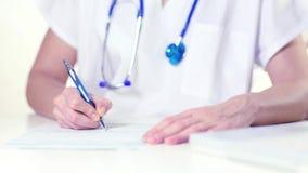 Doutor fêmea que escreve uma prescrição vídeos de arquivo