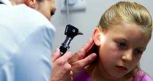 Doutor fêmea que examina a orelha paciente com otoscope filme
