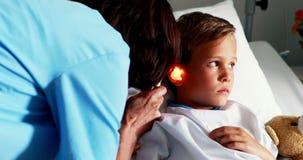 Doutor fêmea que examina a orelha paciente com otoscope vídeos de arquivo