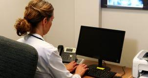 Doutor fêmea que examina um raio X filme
