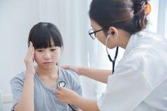 Doutor fêmea que examina uma menina fotografia de stock
