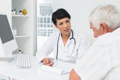 Doutor fêmea que explica relatórios ao paciente superior fotografia de stock