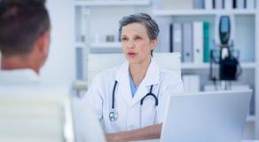Doutor fêmea que fala com seu paciente fotografia de stock