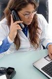 Doutor fêmea que fala no telefone de pilha Fotos de Stock Royalty Free