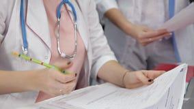Doutor fêmea que faz o documento no escritório Terapeuta novo que enche a lista de verificação médica que senta-se na mesa Cuidad vídeos de arquivo