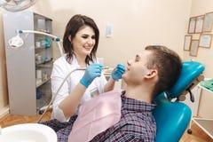Doutor fêmea que faz o trabalho dental ao paciente masculino na sala dental fotos de stock royalty free