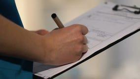Doutor fêmea que faz um registro, escrevendo para baixo a prescrição da medicamentação, close-up vídeos de arquivo