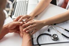 Doutor fêmea que guarda as mãos do paciente masculino superior fotos de stock royalty free