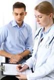 Doutor fêmea que guarda o formulário de candidatura ao consultar o paciente do homem no escritório do hospital Conceito da medici fotos de stock