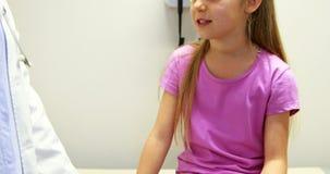 Doutor fêmea que interage com uma menina doente video estoque