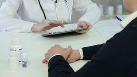 Doutor fêmea que introduz os dados do paciente no informe médico eletrônico no PC da tabuleta vídeos de arquivo