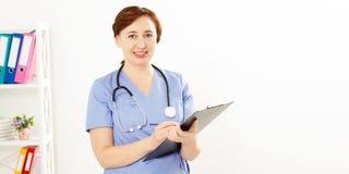 Doutor fêmea que levanta no escritório médico com estetoscópio e dobrador Seguro médico fotografia de stock royalty free