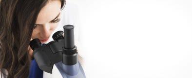 Doutor fêmea que olha através de um microscópio Fotografia de Stock Royalty Free