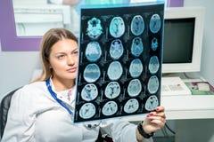 Doutor fêmea que olha um raio X em seu escritório fotografia de stock royalty free