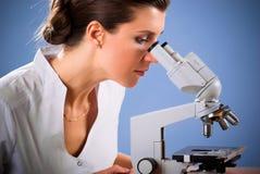 Doutor fêmea que trabalha com um microscópio Imagem de Stock