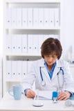 Doutor fêmea que trabalha no escritório Fotografia de Stock Royalty Free