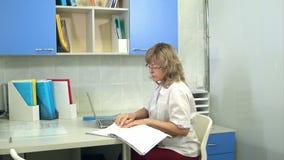Doutor fêmea que usa o portátil que senta-se na mesa em seu escritório video estoque