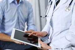 Doutor fêmea que usa o touchpad ou o tablet pc ao consultar o paciente do homem no hospital Medicina e cuidados médicos imagem de stock