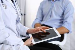 Doutor fêmea que usa o touchpad ou o tablet pc ao consultar o paciente do homem no hospital Medicina e cuidados médicos imagem de stock royalty free