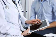 Doutor fêmea que usa o touchpad ou o tablet pc ao consultar o paciente do homem no hospital Medicina e cuidados médicos fotos de stock