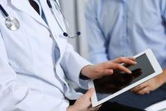 Doutor fêmea que usa o touchpad ou o tablet pc ao consultar o paciente do homem no hospital Medicina e cuidados médicos foto de stock royalty free