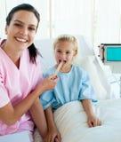 Doutor fêmea que verific a garganta do seu paciente fotografia de stock royalty free