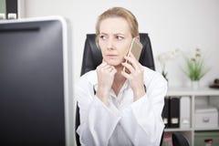Doutor fêmea sério no telefone e vista à esquerda foto de stock