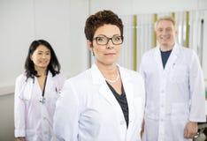 Doutor fêmea seguro Standing With Colleagues no hospital fotografia de stock