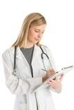 Doutor fêmea With Stethoscope Writing na prancheta foto de stock
