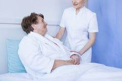 Doutor f?mea bonito novo e paciente superior no hospital imagens de stock royalty free