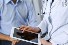 Doutor f?mea que usa o touchpad ou o tablet pc ao consultar o paciente do homem no hospital Medicina e cuidados m?dicos fotografia de stock