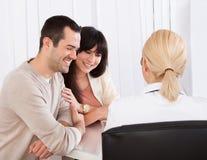 Doutor feliz Discussing With Couple Fotografia de Stock Royalty Free