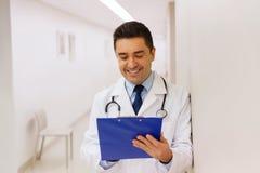 Doutor feliz que escreve à prancheta no hospital Fotografia de Stock
