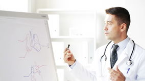 Doutor feliz que mostra o desenho médico na placa da aleta video estoque