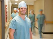 Doutor feliz With Team At Hospital Corridor Imagens de Stock