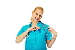 Doutor fêmea de sorriso com o estetoscópio que guarda o termômetro Fotos de Stock Royalty Free