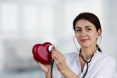 Doutor fêmea de sorriso que guarda o coração vermelho e um estetoscópio Fotografia de Stock