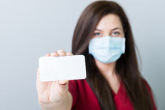 Doutor fêmea que guarda um cartão ou um papel vazio do contato Fotos de Stock Royalty Free