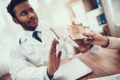Doutor indiano que vê pacientes no escritório A mãe está dando o dinheiro para medicar O doutor está recusando fotografia de stock