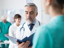 Doutor informes médicos de exame do ` um s do paciente Foto de Stock