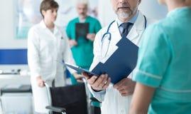 Doutor informes médicos de exame do ` um s do paciente Imagens de Stock