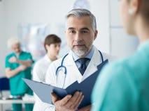 Doutor informes médicos de exame do ` um s do paciente Foto de Stock Royalty Free