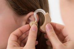 Doutor Inserting Hearing Aid na orelha de uma menina imagem de stock