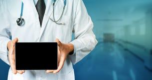 Doutor irreconhecível em um revestimento branco do laboratório com um estetoscópio usando a tabuleta na clínica imagem de stock