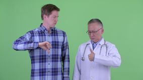 Doutor japonês maduro do homem com o homem novo que tem opiniões diferentes junto video estoque
