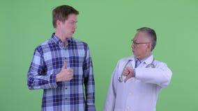 Doutor japonês maduro do homem com o homem novo que tem opiniões diferentes junto vídeos de arquivo