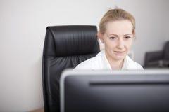 Doutor Looking da fêmea adulta em seu tela de computador Fotos de Stock Royalty Free