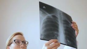 Doutor louro da jovem mulher que olha vidros de tiro do raio X filme